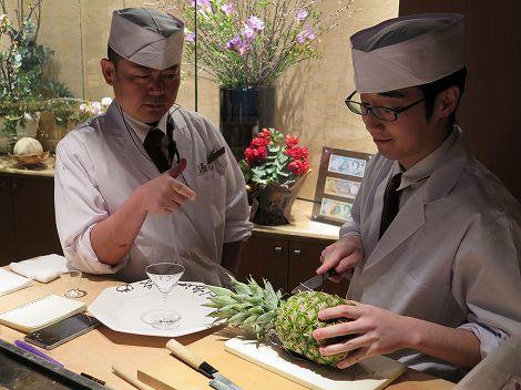 カウンターでは伊藤さん(板前)が 新村さん(板前)にフルーツ飾り切りの 指導中です。