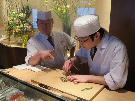 カウンターでは伊藤さんが新村さんに 笹切りの指導中です。
