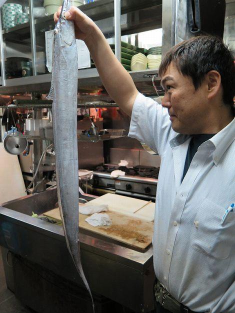 伊藤さんが持っているギラギラ新鮮な太刀魚は この後塩焼きになります