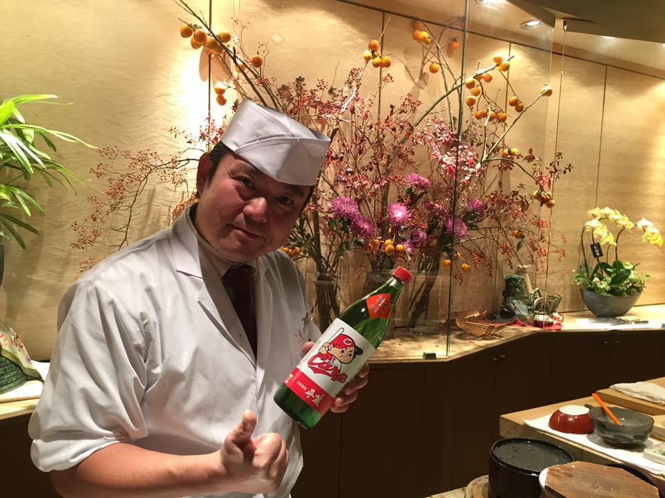 櫻乃峰酒造の 芋焼酎 カープ優勝記念ボトルと伊藤さん(板前)